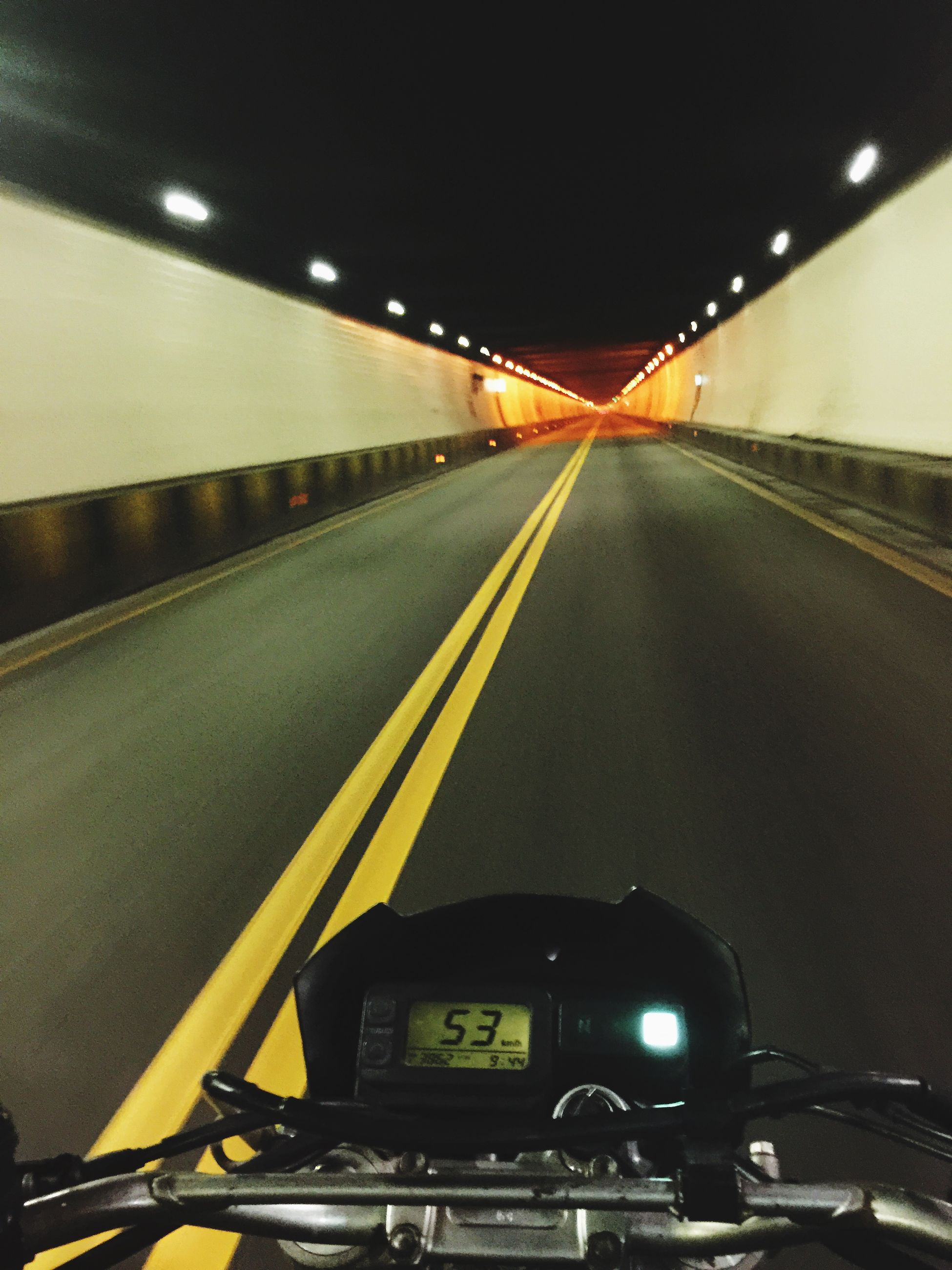 transportation, illuminated, mode of transport, land vehicle, car, indoors, the way forward, night, diminishing perspective, road, lighting equipment, road marking, on the move, travel, traffic, vanishing point, no people, motion, architecture, built structure