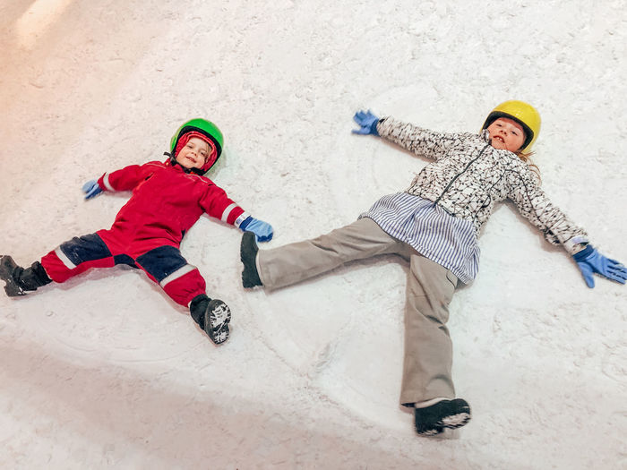 Two People Full Length Winter Males  Snow Child Cold Temperature Togetherness Men Fun Childhood Sport Smiling Happiness Family Clothing Females Warm Clothing Sister Outdoors Snow Angels Making Snow Angels Winter Fun