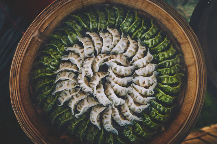 Directly above shot of chinese dumplings arranged in container at market stall