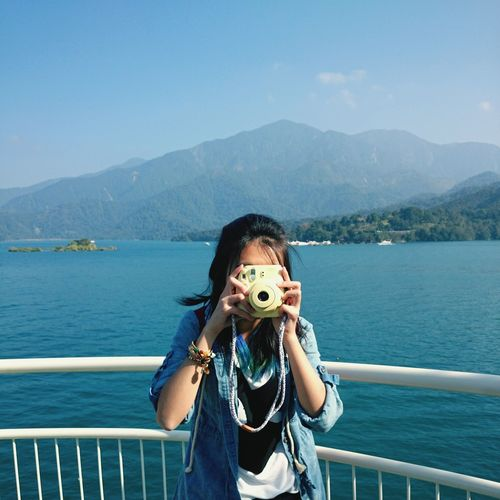 Woman photographing with instant camera while standing against sun moon lake