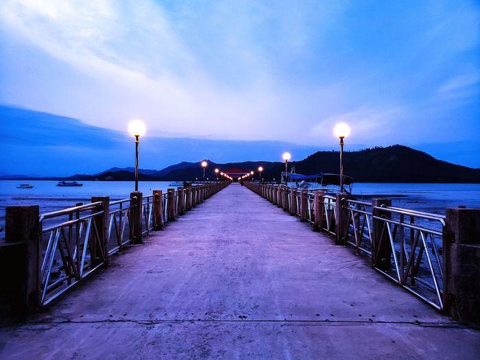 Empty pier on sea against sky at dusk