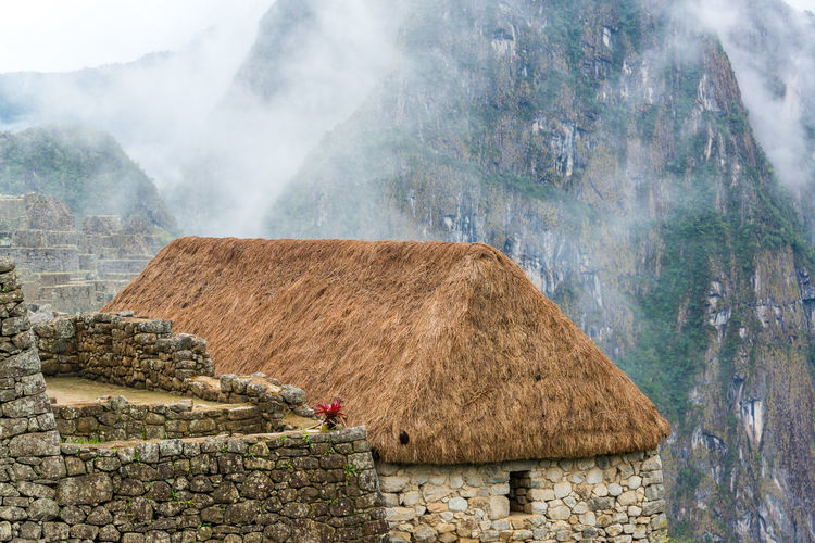 Thatched Roof House Against Rocky Mountains During Foggy Weather At Machu Picchu