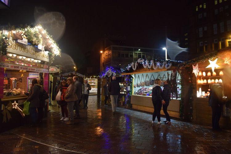 People at illuminated market stall at night