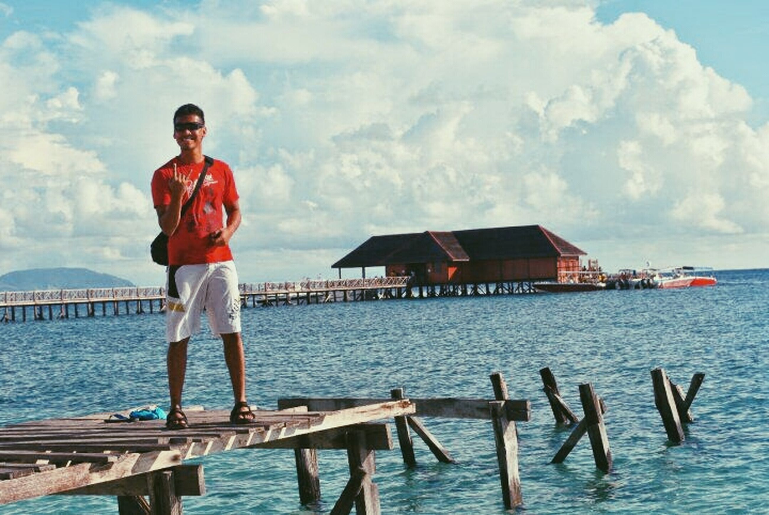 water, pier, standing, casual clothing, sea, lifestyles, sky, leisure activity, built structure, full length, wood - material, person, three quarter length, railing, nautical vessel, waterfront, young adult, nature