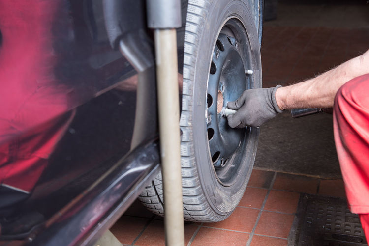 Man Filling Car Tire With Air At Fuel Station