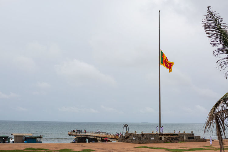 Soldiers raise the Sri Lankan flag in Colombo in Sri Lanka. Flag Sky Patriotism Water Nature Cloud - Sky Sea Day Environment Horizon Over Water Wind Pole Horizon Waving Outdoors Pride No People Beauty In Nature Independence National Icon Colombo Sri Lanka Sri Lanka Tradition