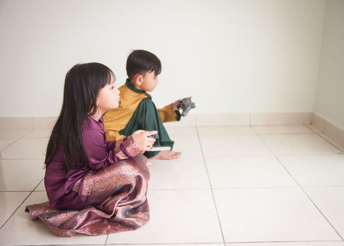 Siblings playing video game while sitting on floor at home