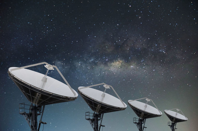 Low Angle View Of Satellite Dishes Against Star Field