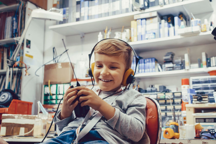 Happy kid with headphones using cb radio in a workshop.