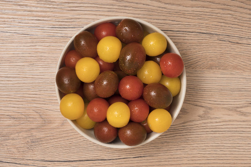 Cherry tomatoes, red,yellow and kamato in ceramic bowl on wooden background. Top view. Fresh; Food; Healthy; Ripe; Red; Vegetable; Cherry; Tomato; Vegetarian; Yellow; Diet; Orange; Variety; Colorful; Different; Health; Green; Organic; Ingredient; Many; Summer; Small; Juicy; Raw; Nature; Tomatoes; Color; Natural; Closeup; Background; Agricul Food And Drink Food Table Freshness Indoors  Wood - Material Still Life High Angle View Healthy Eating Directly Above Close-up No People Wellbeing Multi Colored Fruit Sweet Food Candy Ready-to-eat Bowl Variation Temptation Snack