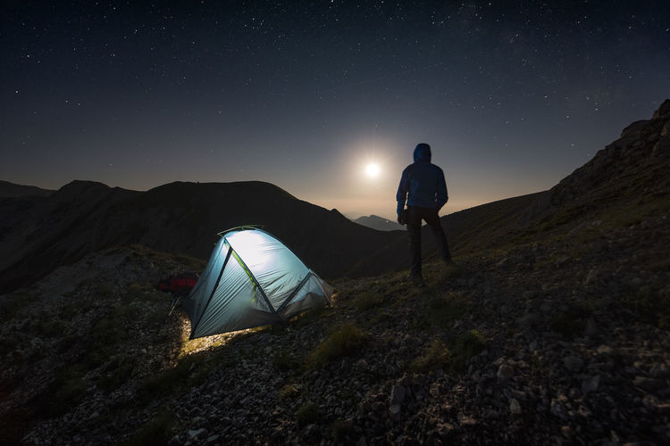 Rear view of silhouette man camping on mountain at night