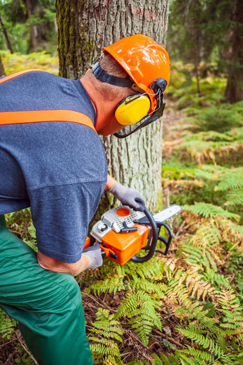 Midsection of man working in forest