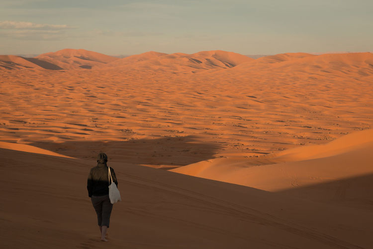 Rear view of woman walking at desert against clear blue sky