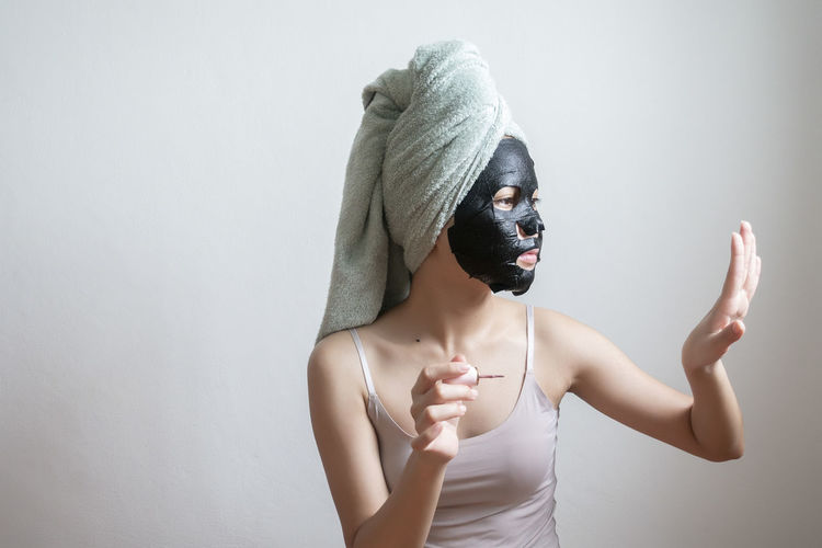 Young Woman Face With Black Facial Mask Applying Nail Polish Against White Background