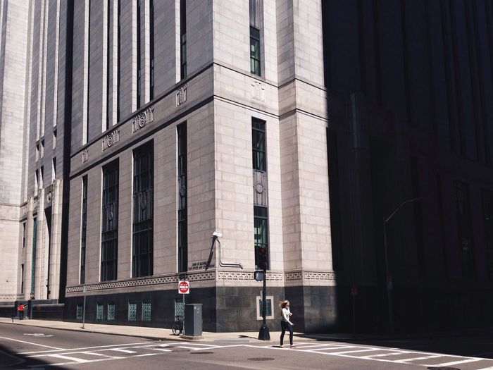 Low angle view of woman crossing road against buildings