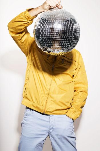 Man holding disco ball against white background