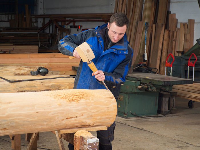 Portrait of man working on wood in workshop