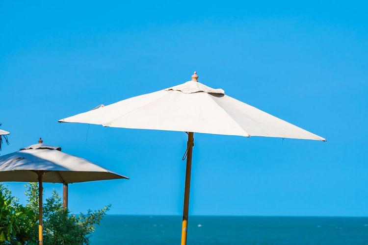 Umbrellas on beach against clear blue sky