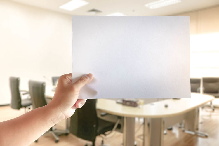 Cropped hand of business person holding blank paper in conference room