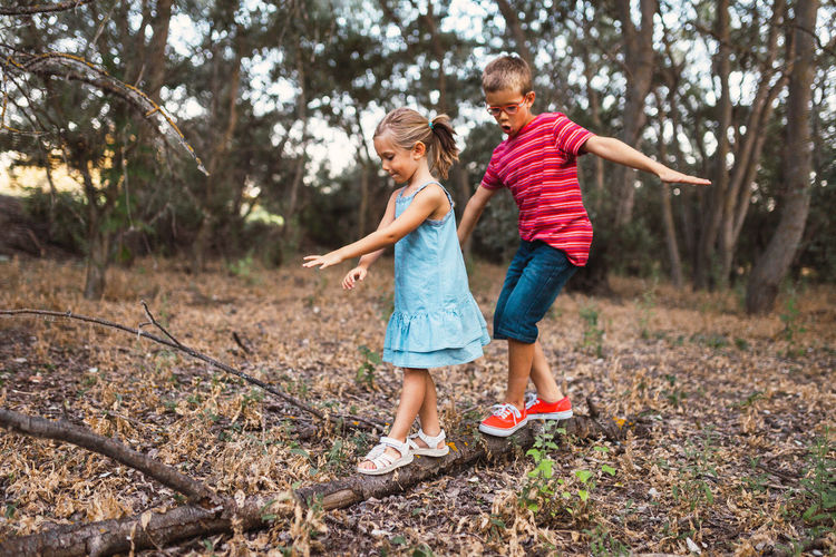 Full length of boy and girl walking on fallen tree