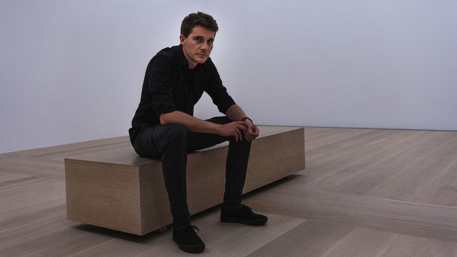 Young man looking away while sitting on hardwood floor against wall