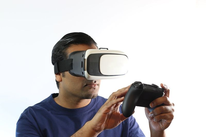 Young man holding gaming remote controller while pressing buttons 360 3D 4K American Angry Controller Cyberspace Display Fun Game Gaming Hologram Indian Man One Person Playing RC Remote Remote Control Student Technology Virtual Reality Virtual Reality Simulator Watching Winning