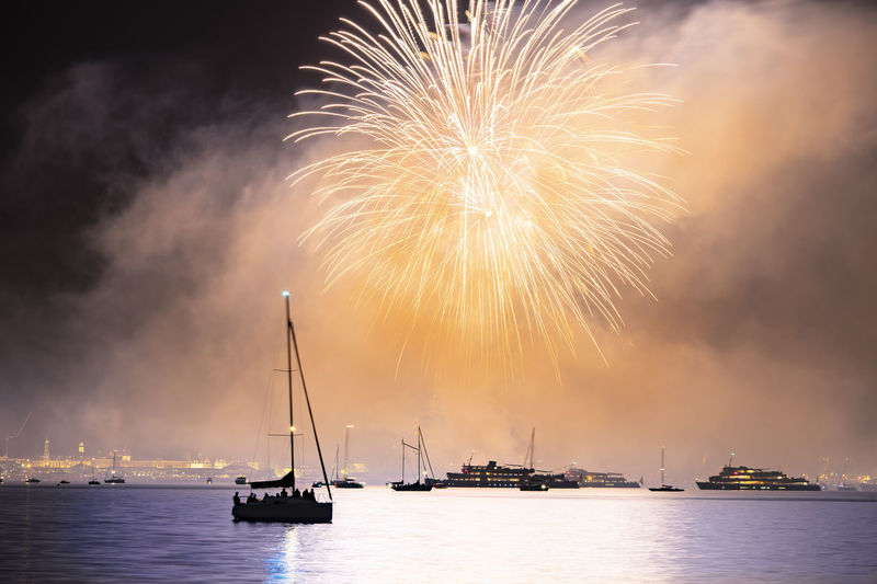 Silhouette boats on sea against firework in sky