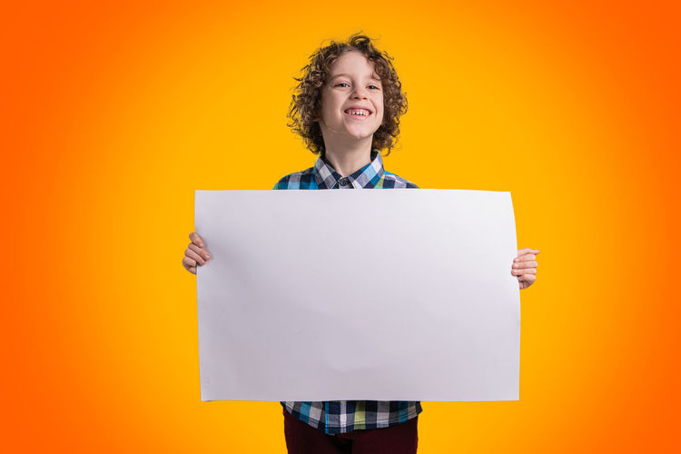 Cute 7 years old guy holding a blank piece of paper leaved empty for copy space. Portrait isolated on an orange background Studio Shot One Person Front View Colored Background Indoors  Smiling Portrait Waist Up Paper Copy Space Cut Out Blank Looking At Camera Holding Standing Communication Yellow Background Orange Background Mouth Open Hairstyle Hair Yellow Males  Boy Guy Sign Concept Child Childhood Children Graphic Style Indoors