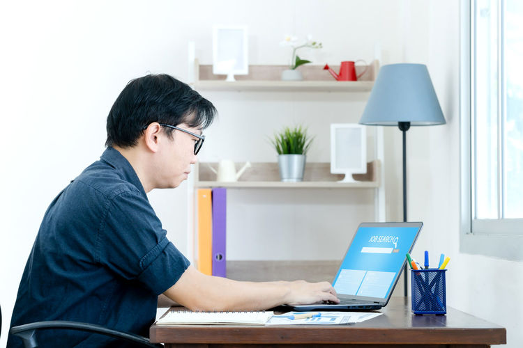 Side view of man using laptop on table