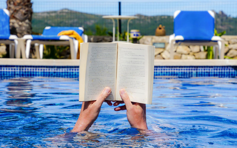 Low section of person reading book on swimming pool