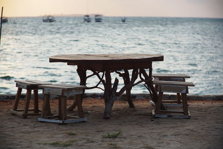 Empty chairs and table at beach during sunset