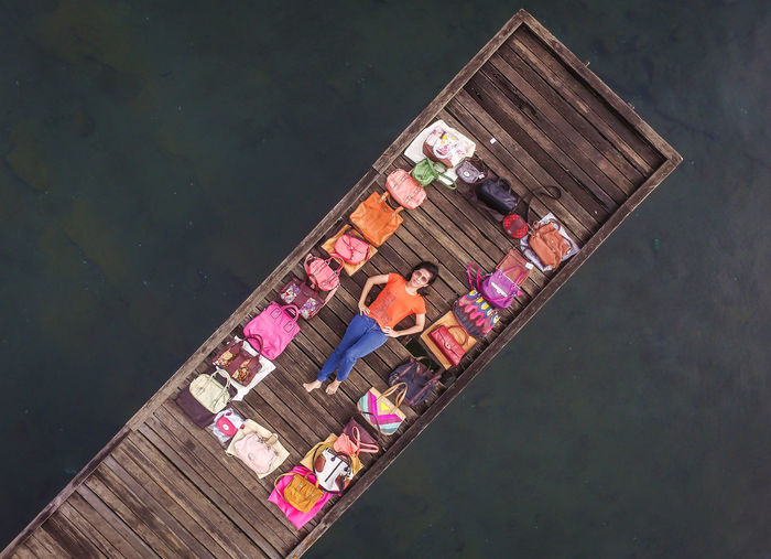 High angle view of woman lying on wooden pier amidst purses over lake