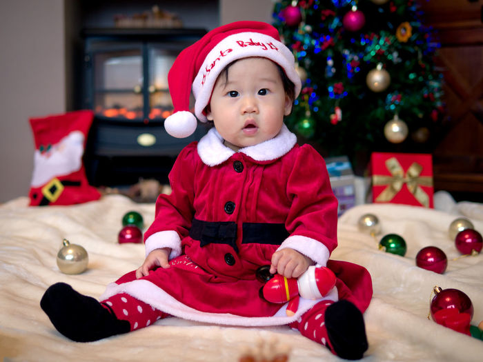 Portrait of cute baby girl wearing santa hat against christmas tree at home