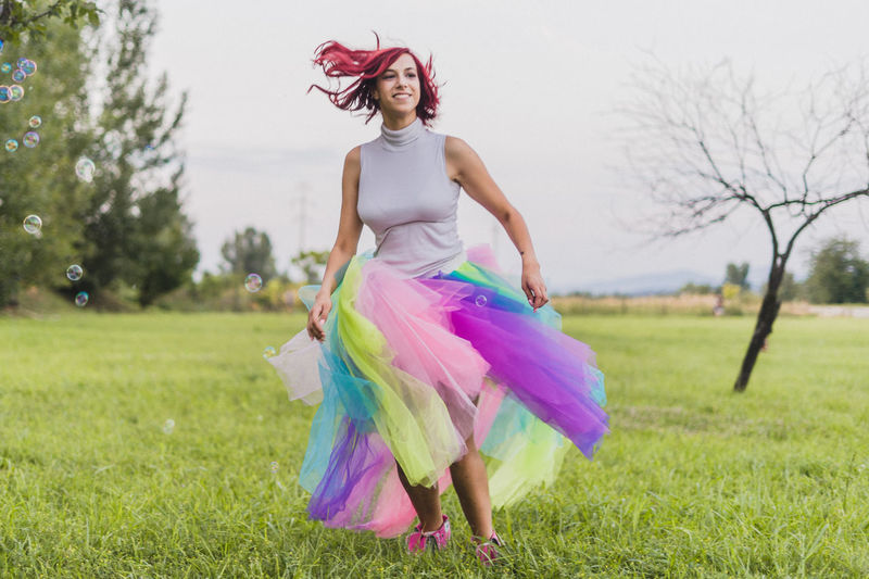 Woman Dancing On Field Against Trees