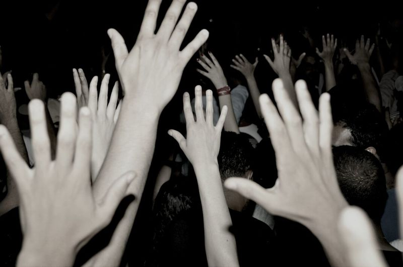 Close-Up Of Raising Hands Over Black Background
