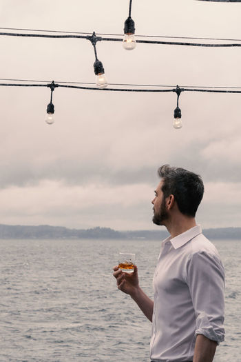 Man drinking scotch under deck lights gazing out to sea. One Person Sky Water Real People Lifestyles Holding Men Leisure Activity Food And Drink Casual Clothing Nature Drink Sea Side View Mid Adult Men Cloud - Sky Day Drinking Alcohol Rocks Glass - Material Longing Romantic Handsome Beard Deck Lights Outdoor Life Success Power Overcast Dramatic Sky Muscular Build