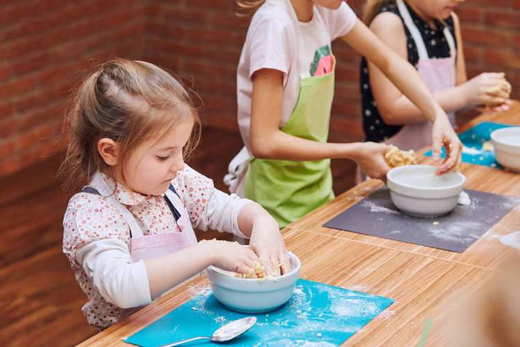 High angle view of girls kneading dough in bowl on table
