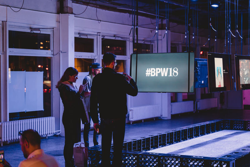Berlin Photo Week 2018 Berlin Photo Week BPW18 EyeEem Real People Text Group Of People Communication Illuminated Men Western Script Lifestyles People Leisure Activity Architecture Railroad Station Information Transportation Women Standing Night Sign Rear View Adult Waiting