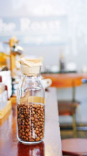 Close-up of roasted coffee beans in jar on wooden table