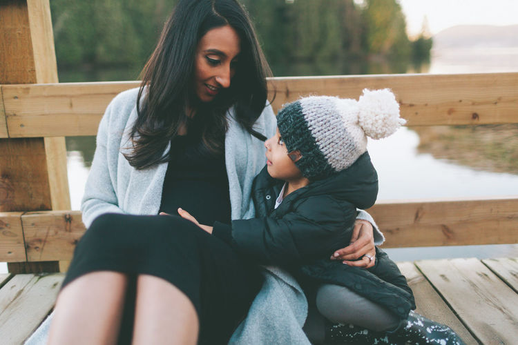 A mother and her son sitting together on a bridge. Mother Son Woman Child Boy Together Family Outdoors Sunset Love Happy Sitting Indian Asian  Diverse