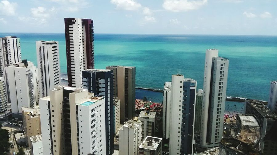 High Angle View Of Cityscape By Sea Against Sky