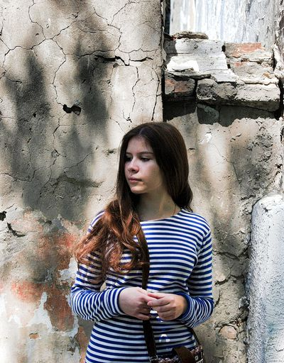 Young woman looking away while standing against weathered wall