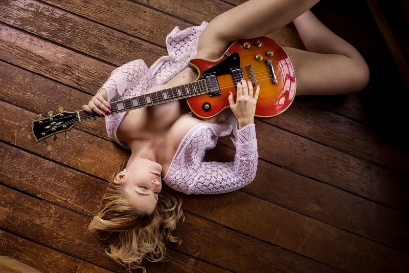 High angle view of seductive woman holding guitar while lying on floor