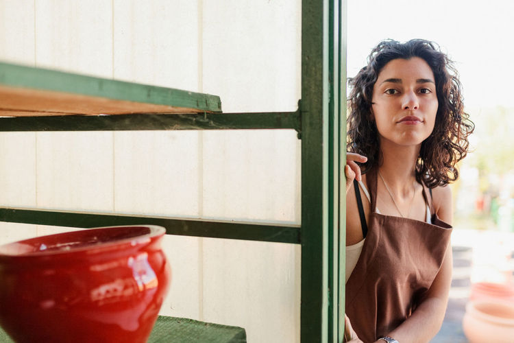 Portrait of beautiful young woman standing against window in pottery shop