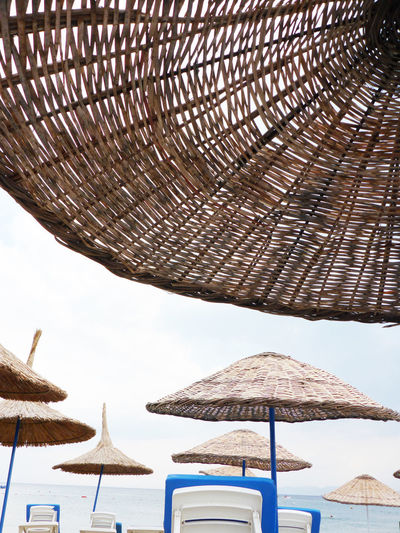 White beach chairs and wicker umbrellas at the beach in Sarimsakli, Turkey Aegean Sea Form Turkey Wicker Ayvalık Beach Beach Chairs Beach Umbrella Beachphotography Close-up Day No People Outdoors Parasol Protection Sarimsakli Shade Sky Straw Sunshade Thatched Roof Tourism Umbrella Vacation White
