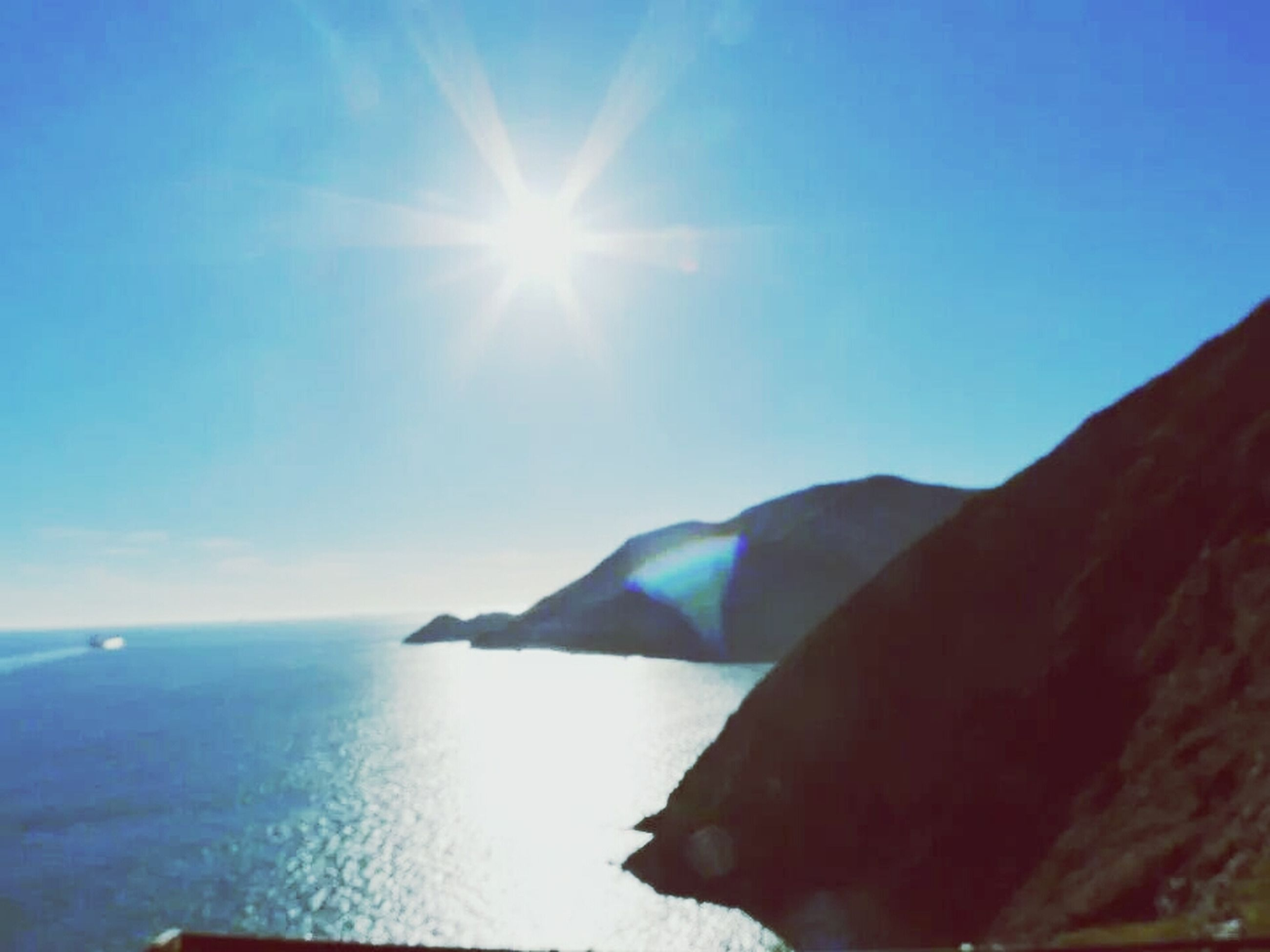 sea, water, sun, scenics, tranquil scene, sunbeam, beauty in nature, sunlight, tranquility, blue, horizon over water, nature, sky, lens flare, rock - object, idyllic, sunny, mountain, day, outdoors