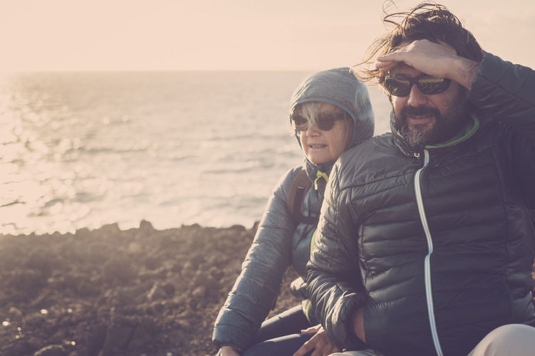 Couple of people enjoying excursion along the sea. Winter time and cold. Mother and son.Horizon over water. Togetherness Two People Lifestyles Water Leisure Activity Sea Glasses Emotion Bonding Love Men Real People Adult Males  Smiling Young Men Sky Nature Casual Clothing Couple - Relationship Positive Emotion Mature Men Warm Clothing Horizon Over Water Outdoors Cold Temperature Hiking Excursion Nature Sunglasses Mother And Son Family Hobby