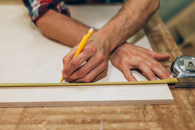 Midsection of carpenter measuring plank at workshop