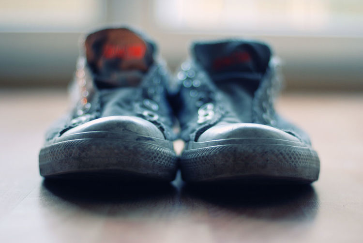 Close-up of shoes on hardwood floor at home