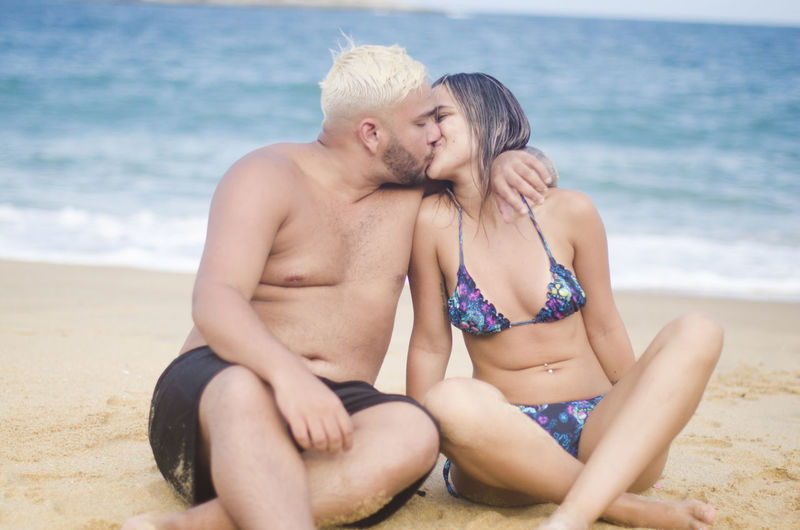Two People Beach Couple - Relationship Sea Land Togetherness Heterosexual Couple Water Love Sitting Adult Shirtless Men Emotion Bonding Women Sand Trip Positive Emotion Beautiful Woman Arm Around